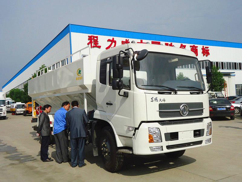 农业厂领导正在工程师指导下操作东风天锦散装饲料运输车