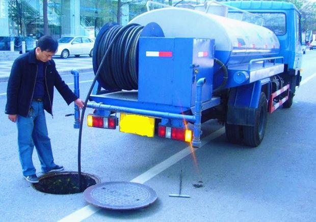 环卫工作正在做高压清洗车疏通下水道
